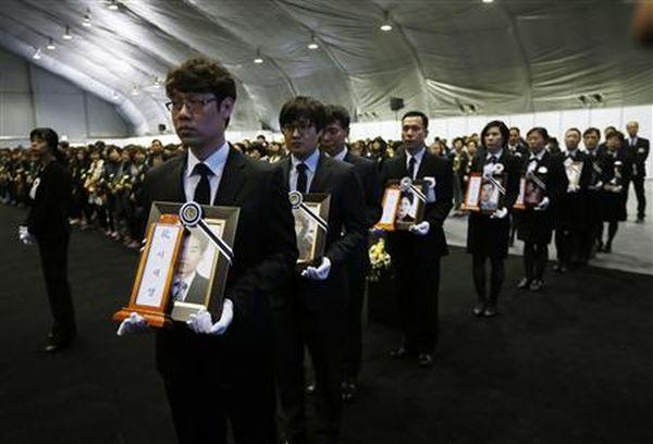 合同焼香所で旅客船セウィル号沈没事故犠牲者の写真を手にその死を悼む遺族ら=29日、韓国・安山(ロイター)