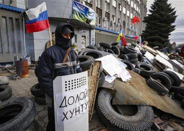 ウクライナ東部ルガンスクの治安機関前に築いたバリケードを守る親ロシア派(ロイター)