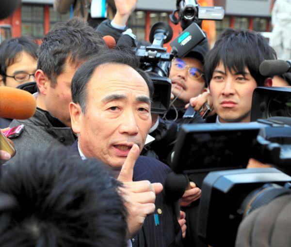 開校予定だった小学校前で、籠池氏(中央)は報道陣に囲まれた=9日、大阪府豊中市