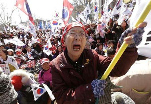 「親朴派」....憲法裁の罷免決定を受けて、太極旗を手に泣き叫ぶ朴大統領の支持者たち=10日、ソウル中心部(AP)