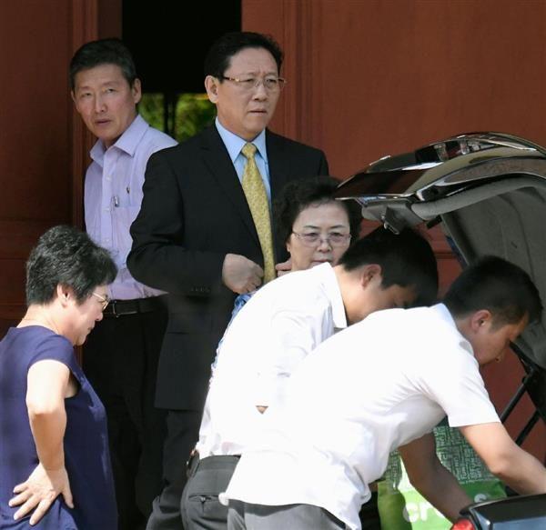 マレーシア政府から国外追放を通告され、クアラルンプールの大使館を出る北朝鮮の姜哲駐マレーシア大使(左から3人目)。左奥は高官代表団の広報担当リ・ドンイル氏=6日(共同)
