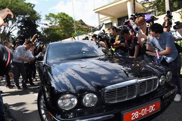 大勢の報道陣に取り囲まれてクアラルンプールの大使館を出る、北朝鮮の姜哲駐マレーシア大使を乗せた車=6日(共同)