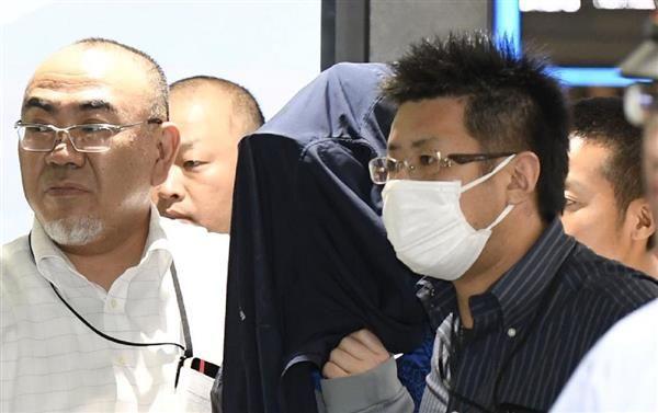 福岡市の金塊窃盗事件で、博多署に移送される容疑者(中央)=22日午後10時36分、JR博多駅