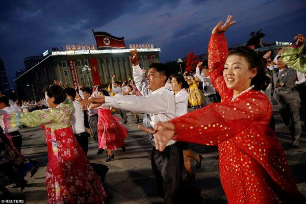 大成功お祝い中の馬鹿北朝鮮市民たちが踊りながらと歌う:『♪♪♪「偉大なる指導者」, 君がなしで我々も生きられないわ...♪♪♪』