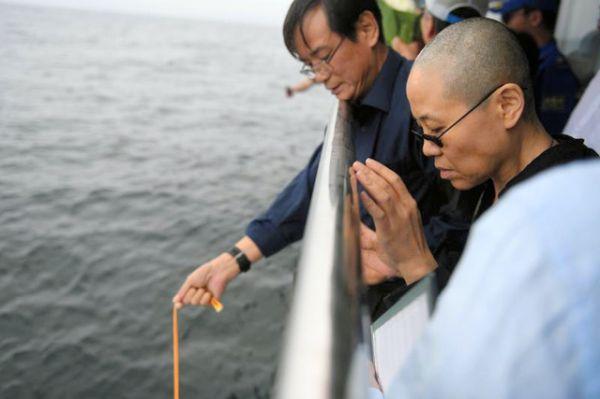 15日、劉暁波氏の遺灰が入ったとみられる骨つぼを船から海に入れる遺族ら。手前は劉氏の妻の劉霞氏(遼寧省瀋陽市提供)