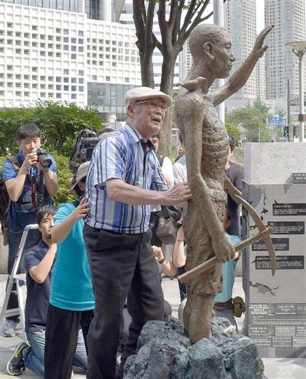 12日、ソウルの竜山駅前に設置された労働者像に触れる元徴用工の金漢洙さん(共同)