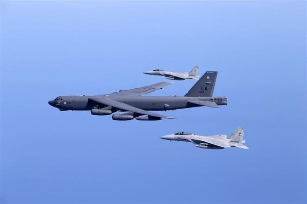 共同訓練する航空自衛隊のF15戦闘機と米空軍のB52戦略爆撃機=27日、日本海上空(航空自衛隊提供) (2)
