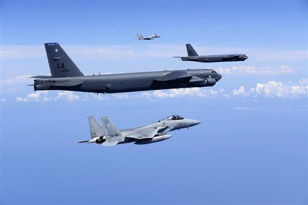 共同訓練する航空自衛隊のF15戦闘機と米空軍のB52戦略爆撃機=27日、日本海上空(航空自衛隊提供)